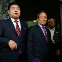 North Korean Ambassador to Mexico Kim Hyong Gil (center) stands at the door of the North Korean Embassy in Mexico City on Friday after addressing the media. | REUTERS