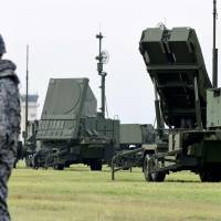 A member of the Air Self-Defense Force stands guard next to a PAC-3 surface-to-air missile launch system during a temporary deployment drill at U.S. Air Force's Yokota Air Base in Fussa, on the outskirts of Tokyo. | AFP-JIJI