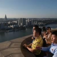 North Korean tourists look out over Pyongyang from atop the Juche Tower on Wednesday. | AFP-JIJI