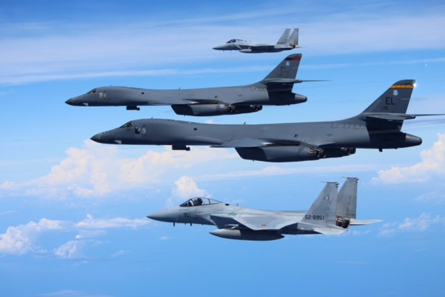 Air Self-Defense Force F-15 fighter jets (top and bottom) conduct an exercise with U.S. Air Force B-1B Lancer bombers flying from Andersen Air Force Base in Guam, in the skies above the East China Sea on Saturday. | REUTERS
