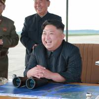 North Korean leader Kim Jong Un watches the launch of a Hwasong-12 intermediate-range ballistic missile in this photo released Saturday. | REUTERS