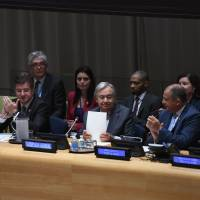 United Nations Secretary-General Antonio Guterres (second from right) is applauded after opening the signing ceremony for the Treaty on the Prohibition of Nuclear Weapons on Wednesday.   AFP-JIJI