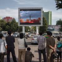 People watch as a screen shows footage of the launch of a Hwasong-12 rocket, beside a billboard advertising North Korea's Pyeonghwa Motors (right), in Pyongyang on Saturday. North Korea said it was seeking military 'equilibrium' with the United States as leader Kim Jong Un vowed to complete Pyongyang's nuclear program. | AFP-JIJI