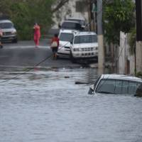 A car is stuck in a flooded street in Santurce, in San Juan, Puerto Rico, on Thursday. Puerto Rico braced for potentially calamitous flash flooding on Thursday after being pummeled by Hurricane Maria, which devastated the island and knocked out the entire electricity grid. | AFP-JIJI