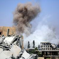 Smoke billows in Raqqa on Monday as Syrian Democratic Forces (SDF), a U.S. backed Kurdish-Arab alliance, battle to retake the northern Syrian city from the Islamic State (IS) group. | AFP-JIJI