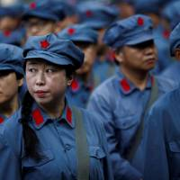 Participants dressed in replica Red Army uniforms stand in formation on Sept. 14 during a Chinese Communist Party team-building course extolling the spirit of the Long March in the mountains outside Jinggangshan. | REUTERS