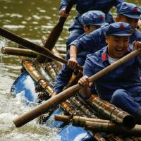 Participants wearing replica Red Army uniforms race on a raft across a lake near Jinggangshan on Sept. 14 during a team-building course organized by the Revolutionary Tradition College. Jinggangshan is considered the 'cradle of the Chinese revolution.' In 1927, it was the birthplace of the Red Army, now known as the People's Liberation Army of China. | REUTERS