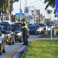 A sheriff's officer directs traffic at a checkpoint near Homestead, Florida, Tuesday. Authorities are only allowing residents and business owners to travel south on U.S. Route 1 towards the Florida Keys. | SCOTT CLAUSE / THE DAILY ADVERTISER / VIA AP