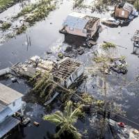 Destroyed homes and vehicles sit in floodwaters after Hurricane Maria in this aerial photograph taken above Hamacao, Puerto Rico, on Monday. Hurricane Maria hit the Caribbean island last week, knocking out electricity throughout the island. The territory is facing weeks, if not months, without service as utility workers repair power plants and lines that were already falling apart. | BLOOMBERG