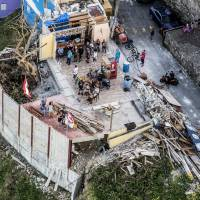 People stand in a bar damaged from Hurricane Maria in this aerial photograph taken above La Perla, San Juan, Puerto Rico, on Monday. | BLOOMBERG
