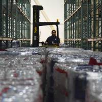 A worker moves bundles of water bottles at a FEMA Central Warehouse after the passage of Hurricane Maria almost one week ago in San Juan, Puerto Rico, Tuesday. The federal government announced it will pick up 100 percent of the costs of for debris removal and other emergency assistance provided to Puerto Rico in the wake of Hurricane Maria. | AP