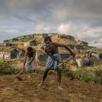 Rohingya Muslim men who crossed over from Myanmar into Bangladesh level the ground before building a shelter at the Balukhali refugee camp Wednesday. | AP