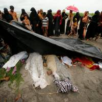 People cover the bodies of Rohingya refugee women and children who died after their boat capsized while crossing the border through the Bay of Bengal, at Shah Porir Dwip, near Teknaf, Bangladesh, Thursday. | REUTERS