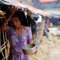 A Rohingya refugee girl collects rain water at a makeshift camp in Cox's Bazar, Bangladesh, Sunday.   REUTERS