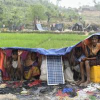 Rohingya refugees protect themselves from the rain in Bangladesh's Balukhali refugee camp on Sunday. Monsoon rain amid a drive to move hundreds of thousands of Muslim Rohingya out of makeshift camps added to the misery of the refugees who have fled violence in Myanmar for Bangladesh.   AFP-JIJI
