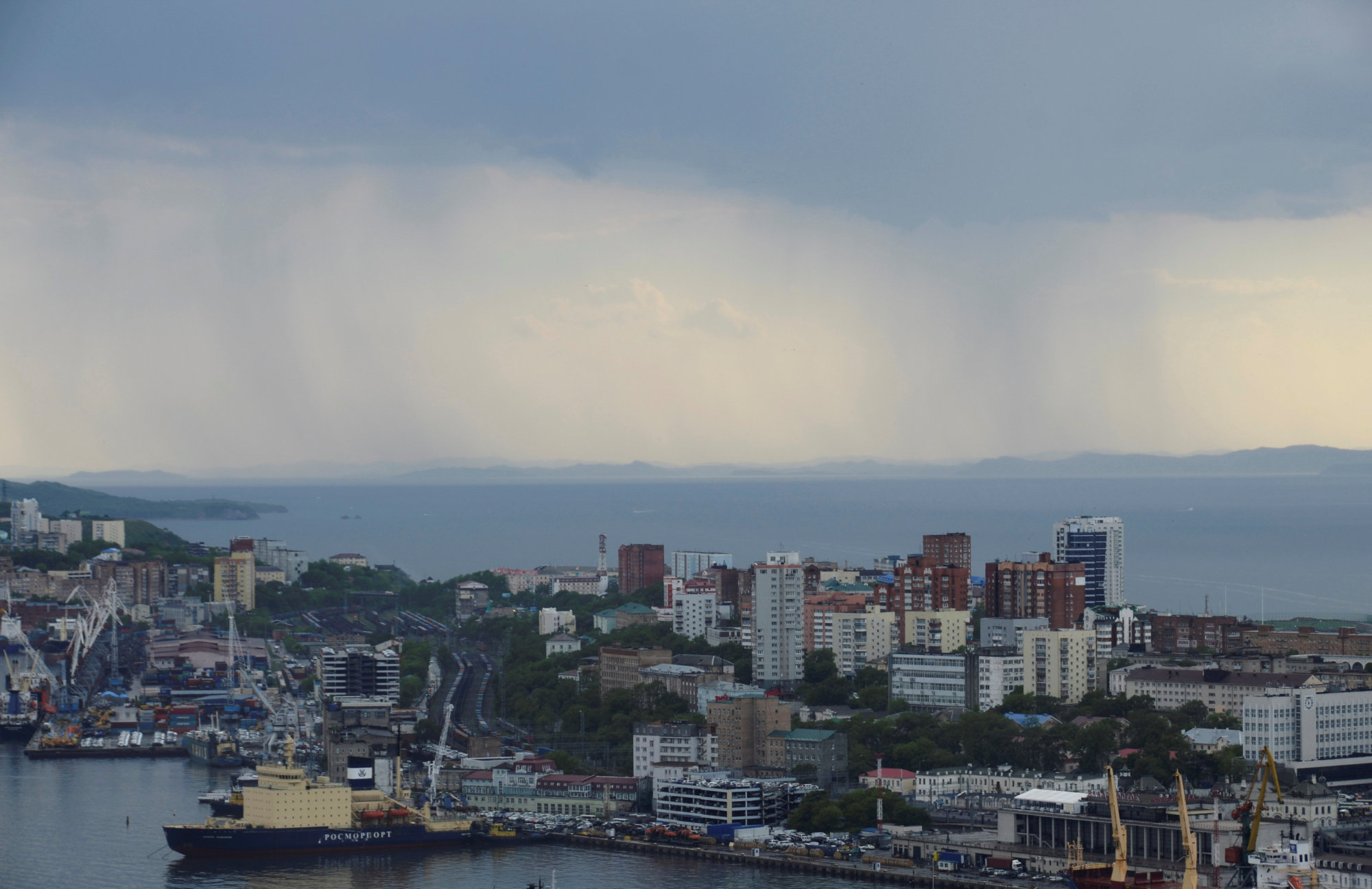 Rain clouds pass over a commercial port in Vladivostok, Russia, on June 8. North Korean ships sailing from Vladivostok and nearby Nakhodka appear to be evading U.N. sanctions. | REUTERS