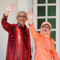 Singapore's ex-speaker of parliament, Halimah Yacob, arrives with her husband to submit her presidential nomination papers in the city-state Wednesday. | REUTERS