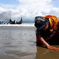 An exhausted Rohingya refugee woman touches the shore in Shah Porir Dwip, Bangladesh, on Monday after crossing from Myanmar by boat through the Bay of Bengal. | REUTERS