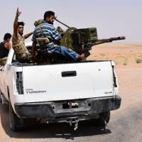 Syrian pro-government forces sit in the back of an armed vehicle in Bir Qabaqib, more than 40 km west of Deir Ezzor, after taking control of the area on their way to Kobajjep in the ongoing battle against Islamic State (IS) group jihadists on Monday. | AFP-JIJI