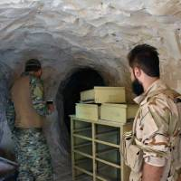 Syrian troops and pro-government gunmen stand inside a cave they seized from Islamic State militants Saturday in the eastern city of Deir el-Zour, Syria. Opposition activists and Syrian state media say government forces are close to breaking a nearly three-year siege imposed by the Islamic State group on parts of the provincial capital of the oil-rich province of the same name. | SANA / VIA AP