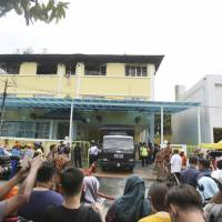 A police truck stands outside an Islamic religious school following a fire on the outskirts of Kuala Lumpur on Thursday. | AP