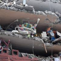 Toys and a baby walker are seen in a collapsed building on Wednesday as the search for survivors from Tuesday's earthquake continued. | AFP-JIJI