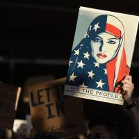 A protester holds a sign at San Francisco International Airport during a January demonstration to denounce President Donald Trump's executive order that bars citizens of seven predominantly Muslim-majority countries from entering the U.S. The Trump administration announced new restrictions after spending months hashing out the details determined to avoid a repeat of the chaos of Trump's first travel ban. | AP