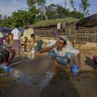Rohingya Muslims, who crossed over from Myanmar into Bangladesh, perform ablution before offering afternoon prayers at the Balukhali refugee camp, Bangladesh, Wednesday. Recent violence in Myanmar has driven hundreds of thousands of Rohingya Muslims to seek refuge across the border in Bangladesh. | AP