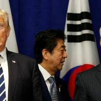 Prime Minister Shinzo Abe walks behind U.S. President Donald Trump and Secretary of State Rex Tillerson at a lunch during the U.N. General Assembly in New York on Thursday. | REUTERS