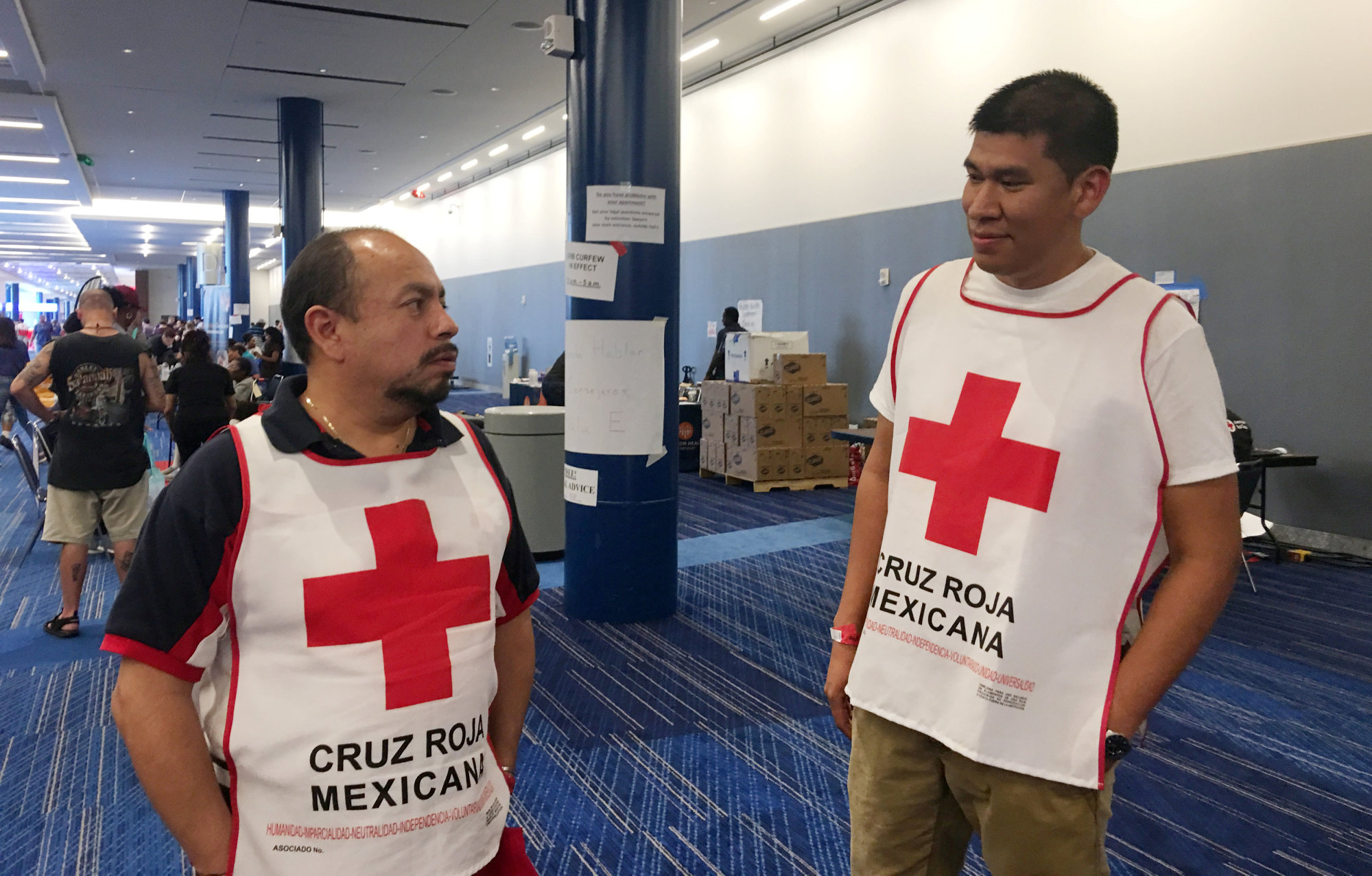 Marco Franco (left), deputy director of Mexican Red Cross disaster relief, talks with Gustavo Santillan, part of a group of 33 Mexican Red Cross volunteers helping victims of Hurricane Harvey, at the George R. Brown convention center in Houston on Monday. | REUTERS