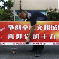 A worker installs a billboard Sunday that reads 'Creates a national civilized city, welcome the 19th Party Congress,' near a residential area in Shanghai, China. The Chinese Communist Party meeting, which is held once every five years, will start on Oct. 18, marking the formal countdown to the gathering at which President Xi Jinping will begin his second five-year term as head of the ruling party. | AP