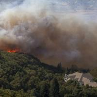 A wildfire burns Sept. 5 through residential areas near the mouth of Weber Canyon near Ogden, Utah. Interior Secretary Ryan Zinke is directing all land managers and park superintendents to be more aggressive in cutting down small trees and underbrush to prevent wildfires. In a memo on Tuesday, Zinke said the Trump administration will take a new approach and work proactively to prevent fires 'through aggressive and scientific fuels reduction management' to save lives, homes and wildlife habitat. | BENJAMIN ZACK / STANDARD-EXAMINER / VIA AP, FILE
