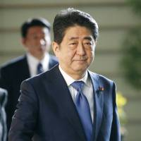 Prime Minister Shinzo Abe walks to his office Monday morning. | KYODO