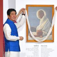 Prime Minister Shinzo Abe and his Indian counterpart, Narendra Modi, decorate a portrait of Mohandas Gandhi in the western Indian city of Ahmedabad on Wednesday. Abe arrived in India earlier the same day to hold talks with Modi and attend a ceremony to mark the start of construction of a new high-speed rail line. | KYODO