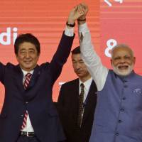 Prime Minister Shinzo Abe and his Indian counterpart, Narendra Modi, hold hands during the ground-breaking ceremony for a high speed rail project in Ahmedabad, India, on Thursday. | AP