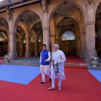 Prime Minister Shinzo Abe is seen walking with Indian Prime Minister Narendra Modi during their visit to the Sidi Saiyyid Ni Jaali mosque in Ahmedabad, India, in this handout photograph released by India's Press Information Bureau on Wednesday. | AFP-JIJI