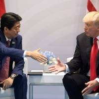 Prime Minister Shinzo Abe shakes hands with U.S. President Donald Trump during a bilateral meeting on the sidelines of the Group of 20 Summit in Hamburg, Germany, in July. | AFP-JIJI