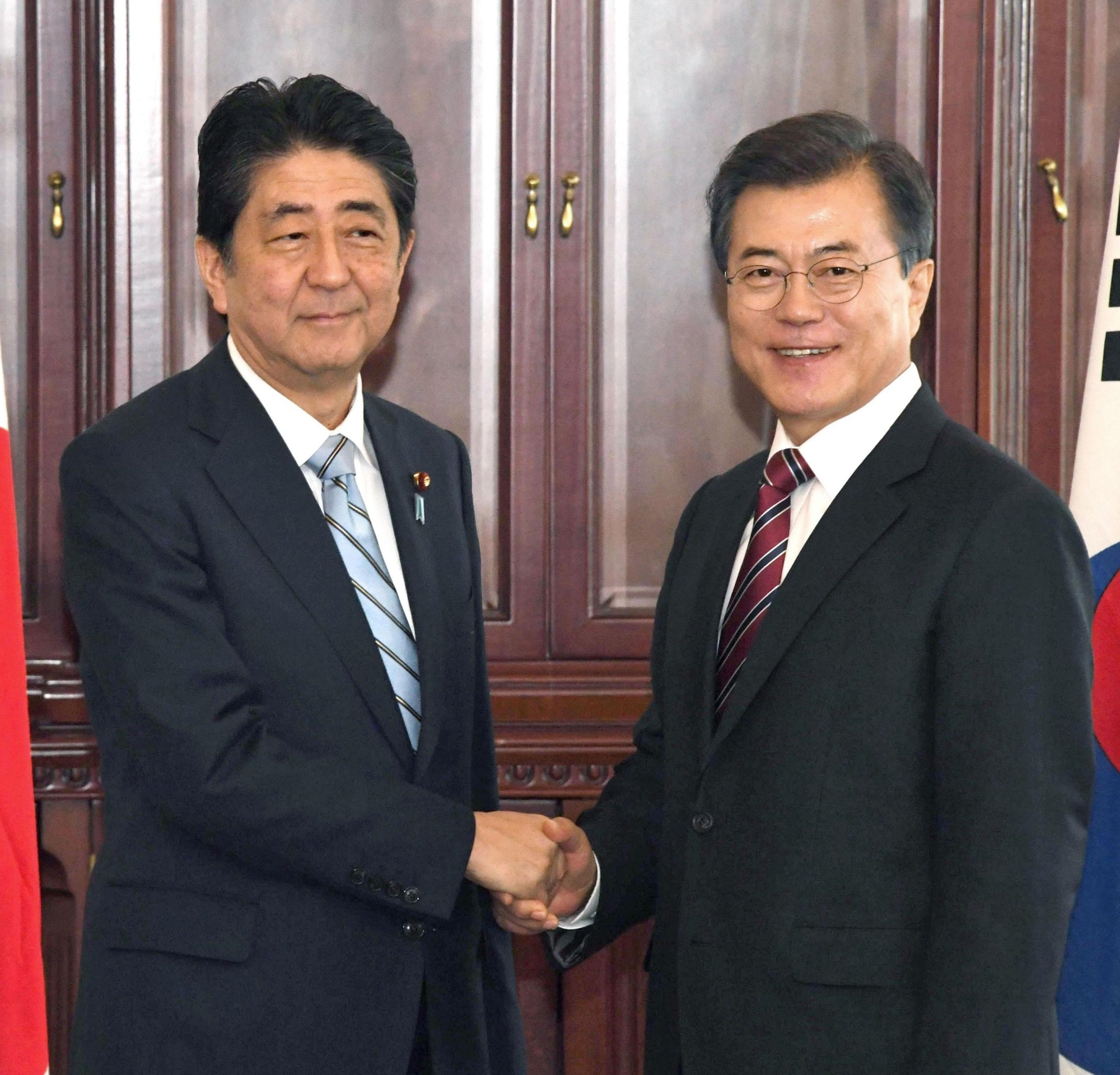 Prime Minister Shinzo Abe and South Korean President Moon Jae-in pose for the media ahead of their talks in Vladivostok, Russia, on Thursday. | KYODO