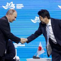 Russian President Vladimir Putin shakes hands with Prime Minister Shinzo Abe at a plenary session called 'The Russian Far East: Creating a New Reality' at the 2017 Eastern Economic Forum at the Far Eastern Federal University on Vladivostok's Russky Island on Thursday. | AP