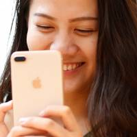 A woman holds a new iPhone 8 Plus after the handsets went on sale at the Apple Store in Tokyo's Omotesando district on Friday. | REUTERS