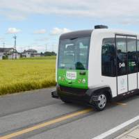 A self-driving bus runs alongside rice paddies in the city of Tochigi during a test run on Saturday. | KYODO