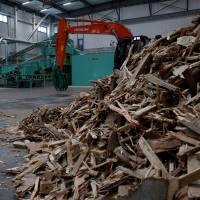 Wood construction waste, set to be made into wood chips, is seen at the Eco Green Holdings factory in Tokyo. | REUTERS