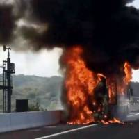 Flames engulf a tour bus on the Shin-Tomei Expressway in Okazaki, Aichi Prefecture, on Saturday after a fire erupted near the engine. No one was injured. | COURTESY OF YASUTOMI KANO / VIA KYODO