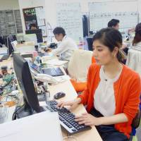 Nanako Shibata works at a staffing agency in Tokyo on July 20. | KYODO