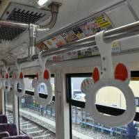 The cat design commemorating the 110th anniversary of the Tamagawa Line is seen on hand straps inside a new tram. | SATOKO KAWASAKI