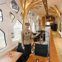 An attendant shows the lounge car of the Train Suite Shiki-shima, operated by JR East, at Ueno Station in Tokyo in March. | CHUNICHI SHIMBUN