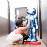 Children play with Vevo, a robot co-developed by Global Bridge Holdings and academics at Gunma University, at a nursery school run by the company in Chiba Prefecture on June 9. | SOCIAL SOLUTIONS