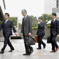 Dentsu Inc. President Toshihiro Yamamoto (left) enters the Tokyo Summary Court on Friday to testify in the advertising company's overwork trial, which was spurred by the suicide of Matsuri Takahshi. | KYODO