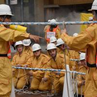 Staff from the U.S. Embassy practice using ropes for rescue operations during an annual disaster drill Friday at the Roppongi Hills complex in Minato Ward, Tokyo. | SATOKO KAWASAKI