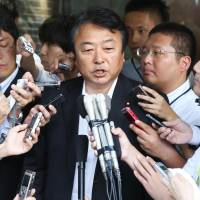 Former Democratic Party lawmaker Yoshihiro Suzuki speaks to reporters Wednesday at the party's headquarters after submitting a written resignation. | KYODO